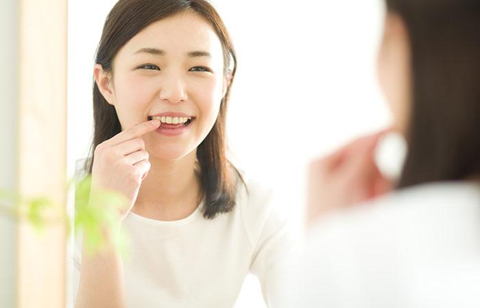 鏡で歯をチェックするロングヘア―の女性