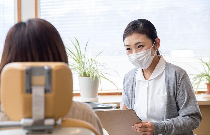 患者に話を聞いている女性歯科助手
