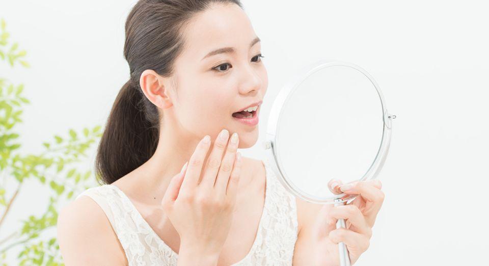 鏡をチェックする白いタンクトップの女性